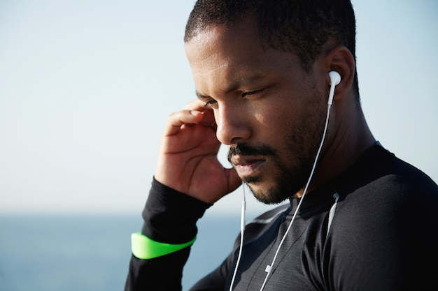 Mens en technologie concept. knap afrikaans amerikaans mannetje dat oortelefoons voor het luisteren aan muziek op zijn mobiele telefoon gebruikt Gratis Foto