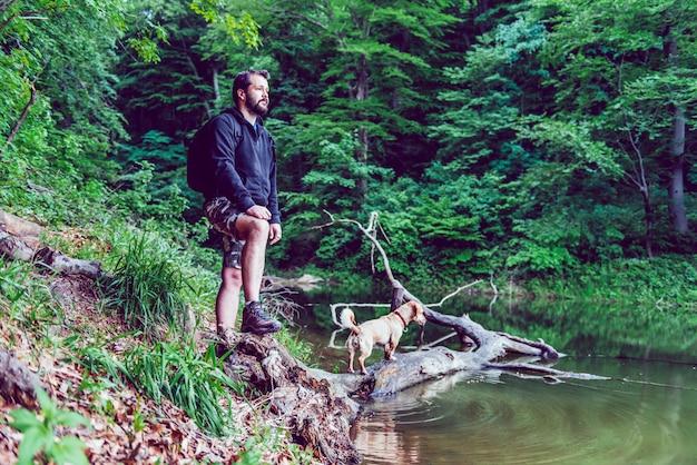 Mens en zijn hond die op meerkust rusten Premium Foto