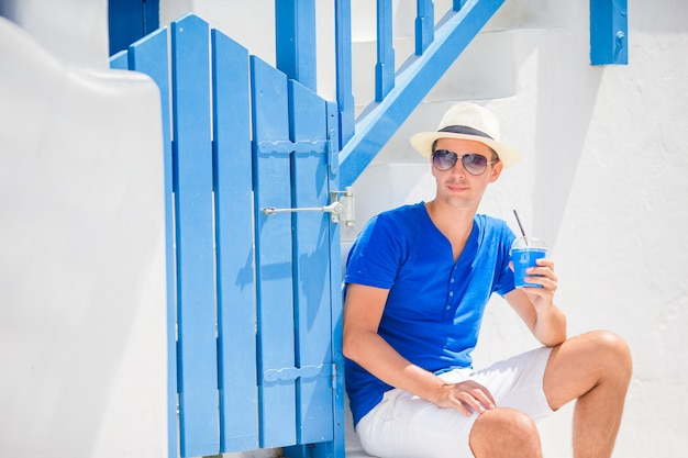 Mens het drinken koffie in griekse straten in openlucht. jonge jongen met hete koffie in openluchtkoffie Premium Foto