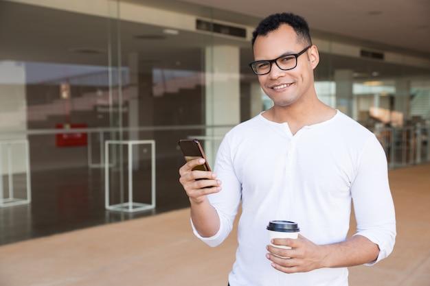 Mens het texting op telefoon, die meeneemkoffie houden, bekijkend camera Gratis Foto