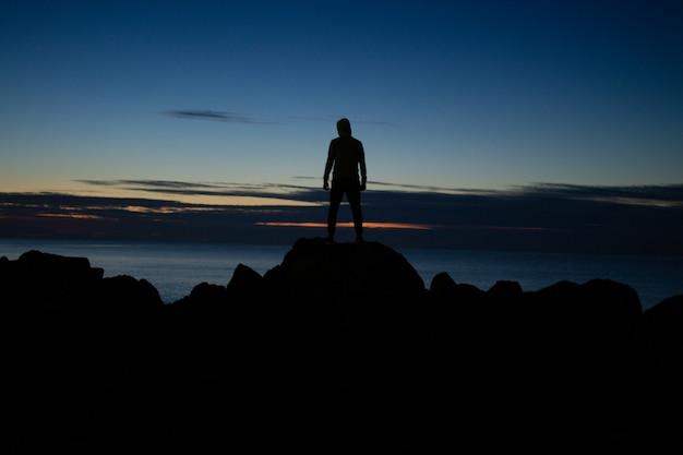Mens in de kap die zich op de rotsen op overzeese achtergrond in avondtijd bevinden Premium Foto