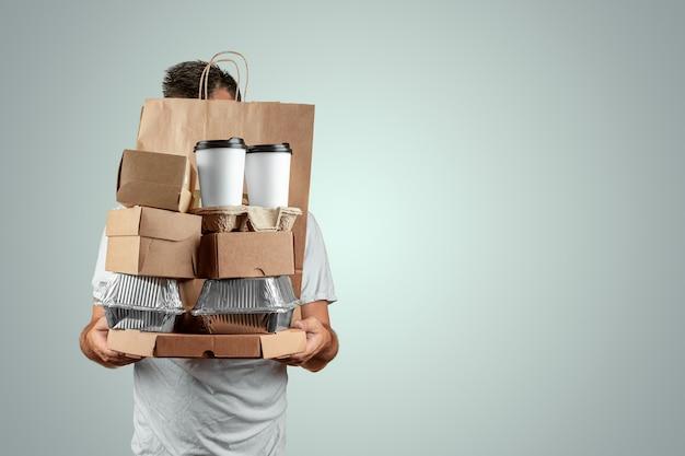 Mens in een heldere t-shirt die een snel voedselorde geeft die op een blauwe achtergrond wordt geïsoleerd Premium Foto