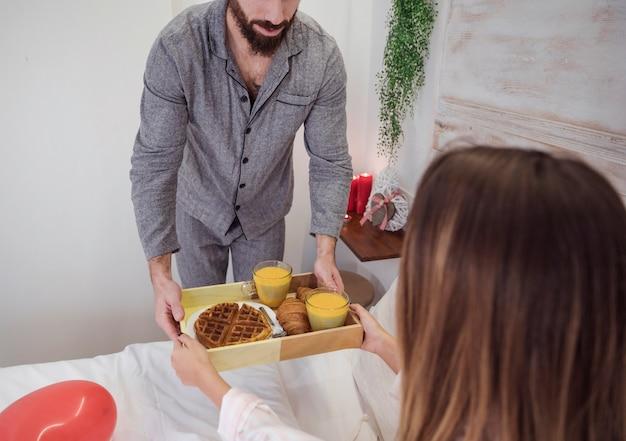 Mens in grijs gevend dienblad met romantisch ontbijt aan vrouw Gratis Foto