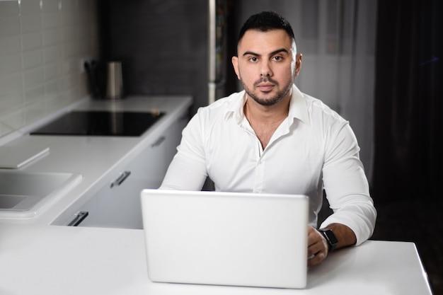 Mens in het witte overhemd websurfing met laptop in huiskeuken Premium Foto