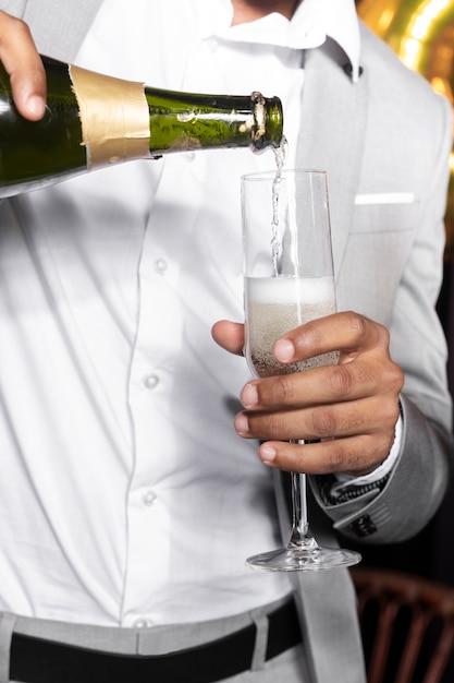 Mens in mooie kostuum gietende champagne in een glas Gratis Foto
