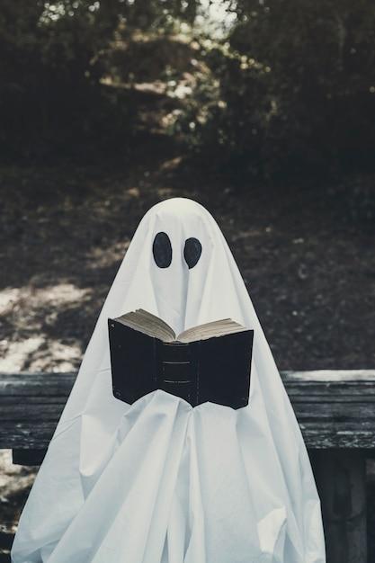 Mens in spookkostuumzitting op bank en lezingsboek Gratis Foto