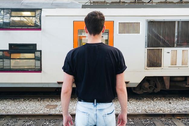Mens in zwarte t-shirt die zich voor spoorwegtrein bevindt Gratis Foto