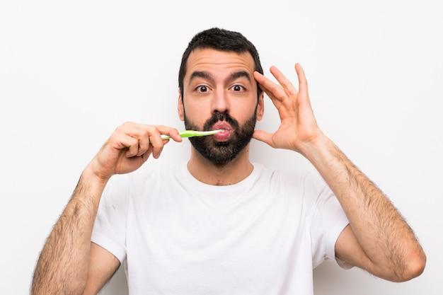 Mens met baard die tanden poetsen die verrassingsgebaar maken Premium Foto