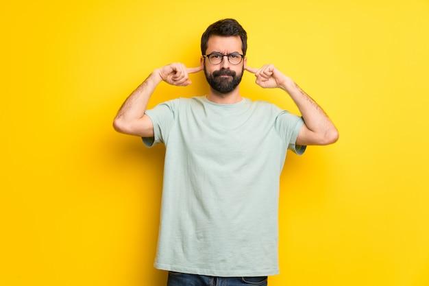 Mens met baard en groen overhemd die beide oren behandelen met handen Premium Foto