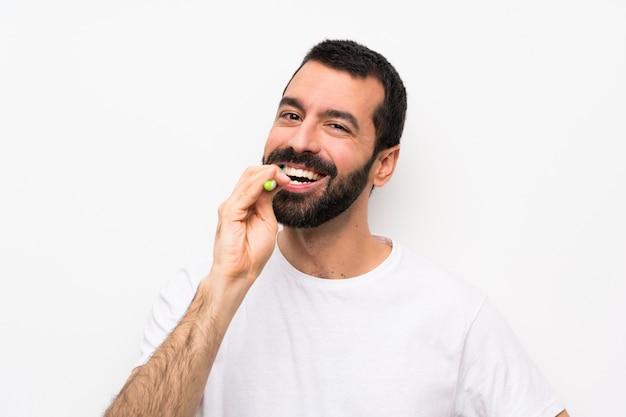 Mens met baard het borstelen tanden over geïsoleerd wit Premium Foto