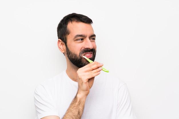 Mens met baard het borstelen tanden over geïsoleerde witte muur Premium Foto