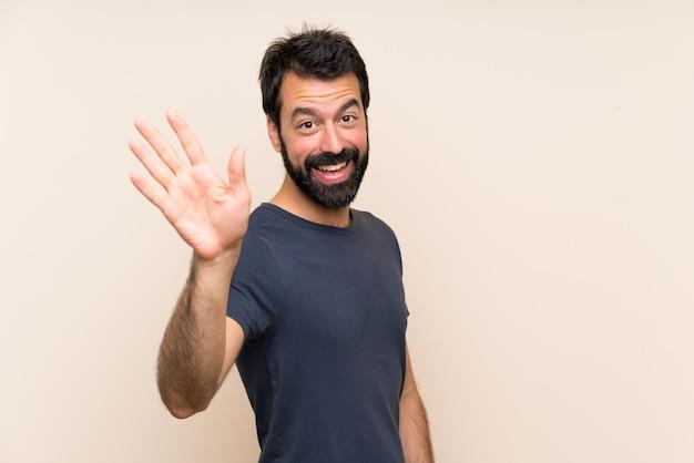 Mens met baard het groeten met hand met gelukkige uitdrukking Premium Foto