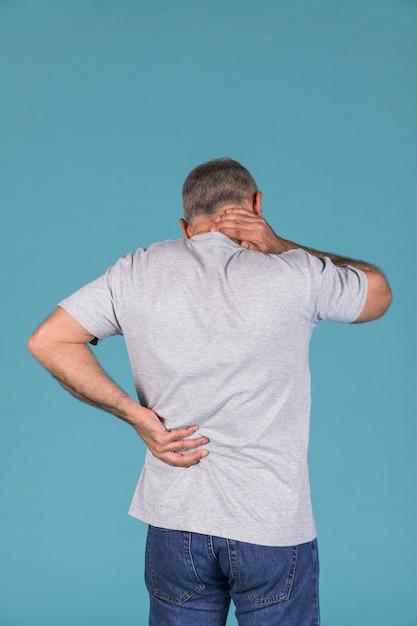 Mens met hals en rugpijn die zich voor blauwe achtergrond bevinden Gratis Foto