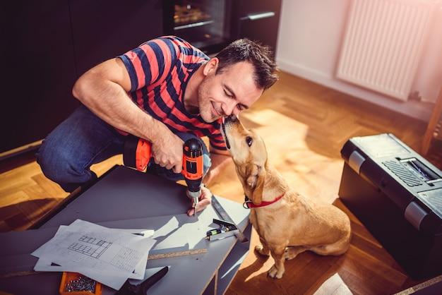 Mens met hond de bouw van keukenkasten en het gebruiken van een draadloze boor Premium Foto