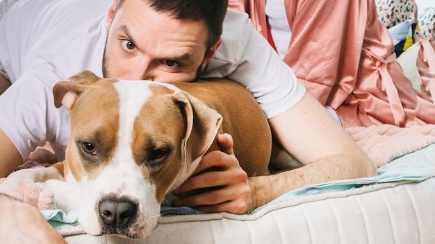 Mens met hond in bed Gratis Foto