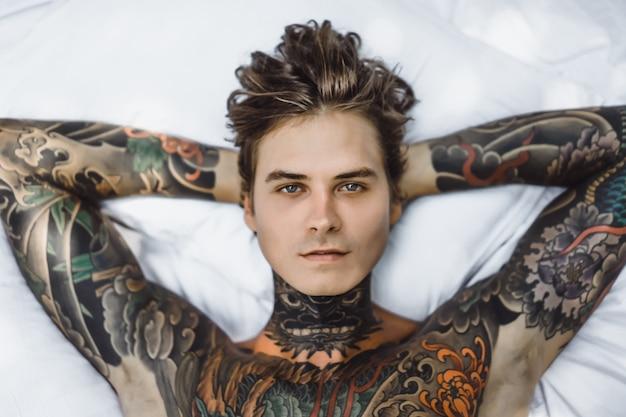 Mens met kleurrijke tatoegeringen die op een wit blad stellen Gratis Foto