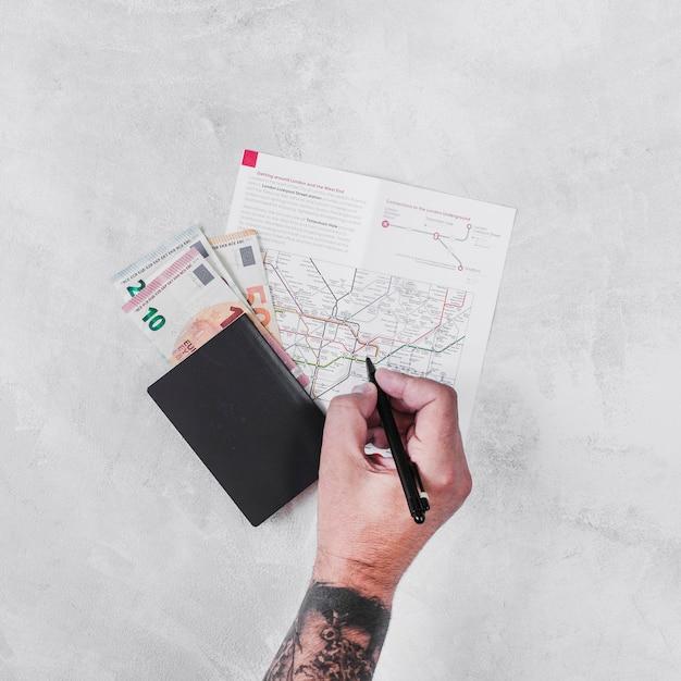 Mens met paspoort en euro nota's die op wegenkaart merken Gratis Foto