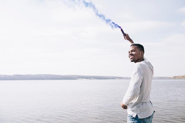Mens met rooktoorts op kust Gratis Foto