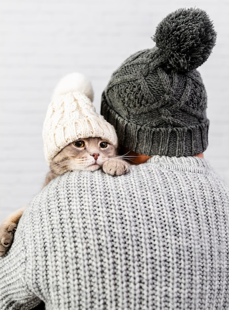 Mens met rug die klein katje houdt Gratis Foto