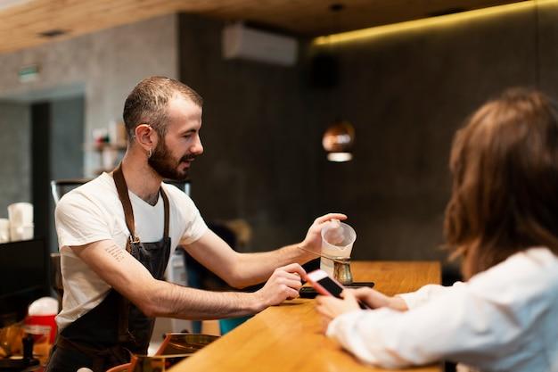 Mens met schort gietend water in koffiepot Gratis Foto