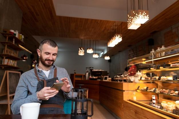 Mens met schort op telefoon in koffiewinkel Gratis Foto
