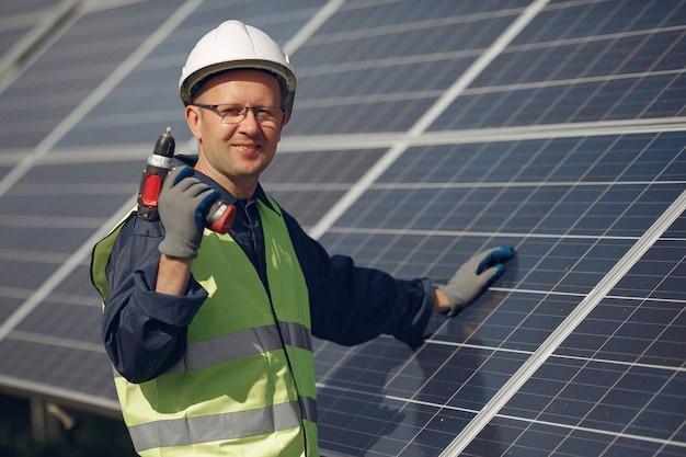 Mens met witte helm dichtbij een zonnepaneel Gratis Foto