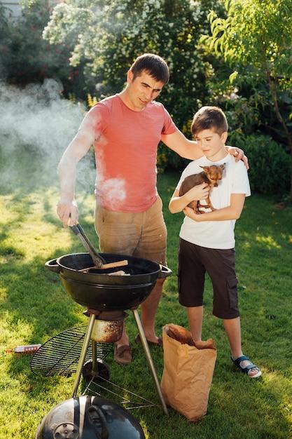 Mens met zijn zoons kokend voedsel op barbecuegrill Gratis Foto