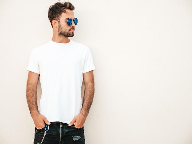 Mens met zonnebril die het witte t-shirt stellen dragen Gratis Foto