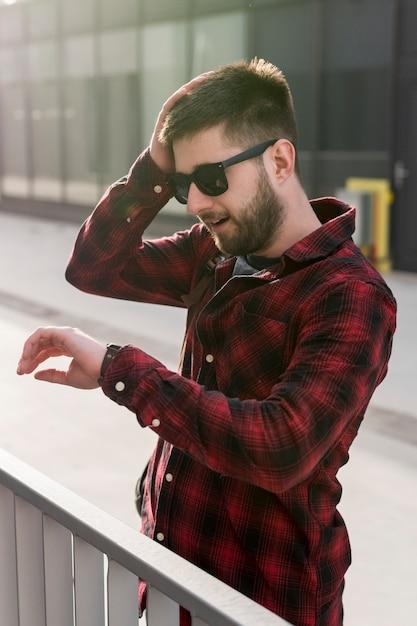 Mens met zonnebril die hoofd houden en horloges bekijken Gratis Foto
