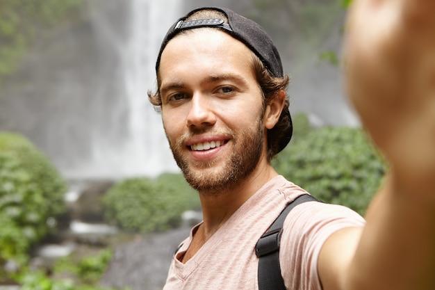 Mens, natuur en toerisme. knappe jonge reiziger in snapback glimlachend vreugdevol tijdens het nemen van selfie, poseren door prachtige waterval in regenwoud Gratis Foto