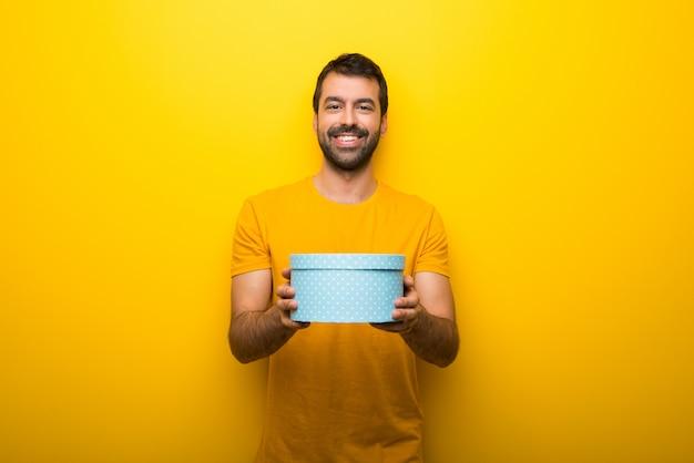 Mens op geïsoleerde trillende gele de giftdozen van de kleurenholding in handen Premium Foto