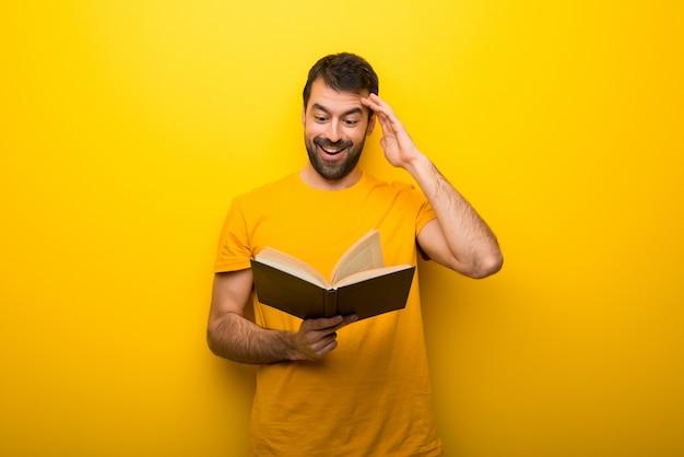 Mens op geïsoleerde trillende gele kleur die een boek houdt en verrast terwijl het genieten van van lezing Premium Foto
