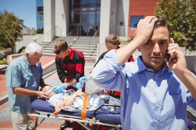 Mens op mobiele telefoon spreken en paramedici die gewonde jongen op achtergrond onderzoeken Gratis Foto