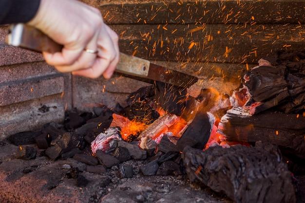 Menselijk hand brandend hout in vuurplaats Premium Foto