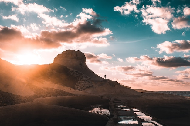 Menselijk silhouet staande op een rotsachtige berg tijdens zonsondergang onder een bewolkte blauwe hemel Gratis Foto