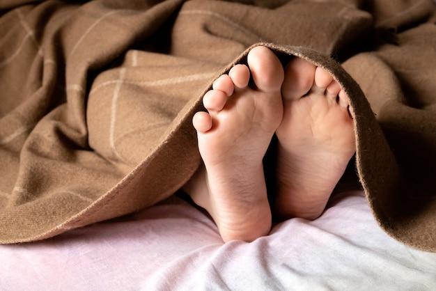 Menselijke blote voeten steken onder de deken vandaan Premium Foto
