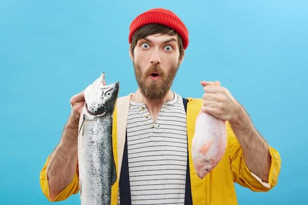 Menselijke gezichtsuitdrukkingen, emoties en gevoelens. grappige verbaasde jonge visser met rode hoed en gele regenjas poseren tegen muur met twee vissen, verrast met mooie vangst Gratis Foto