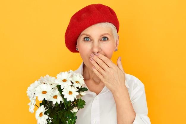 Menselijke gezichtsuitdrukkingen en emoties. portret van blauwogige kortharige vrouw in elegante hoofddeksels die de mond bedekken terwijl hij naar adem snakt Gratis Foto