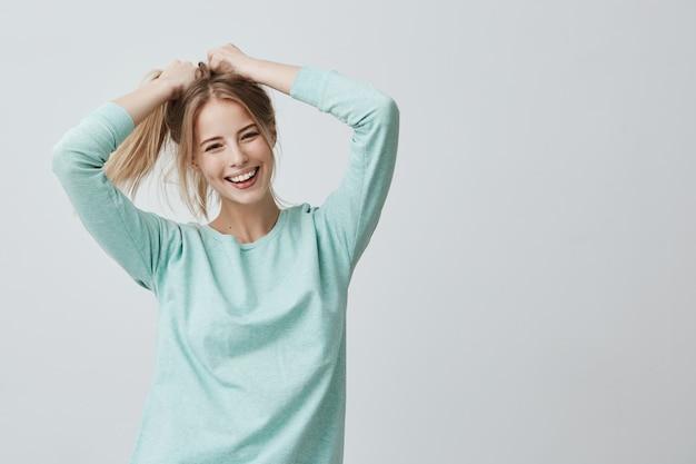 Menselijke gezichtsuitdrukkingen en emoties. positieve jonge mooie vrouw met geverfd blond steil haar in paardenstaart gekleed in casual kleding Gratis Foto
