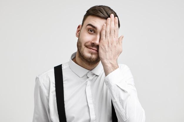 Menselijke gezichtsuitdrukkingen en lichaamstaal. geïsoleerde schot van positieve jonge bebaarde zakenman die de ene helft van zijn gezicht bedekt en vrolijk lacht naar de camera. optica, visie, gezichtsvermogen en oftalmologie Gratis Foto