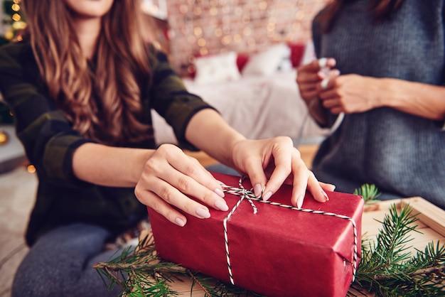 Menselijke hand die een koord op kerstcadeau koppelt Gratis Foto