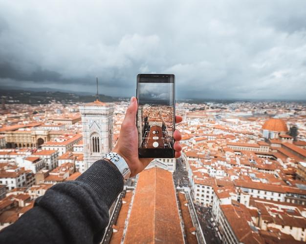 Menselijke hand die een smartphone vasthoudt om een foto van florence te maken Gratis Foto