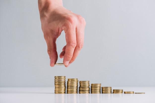 Menselijke hand die gouden muntstukken op weerspiegelend bureau stapelt Premium Foto