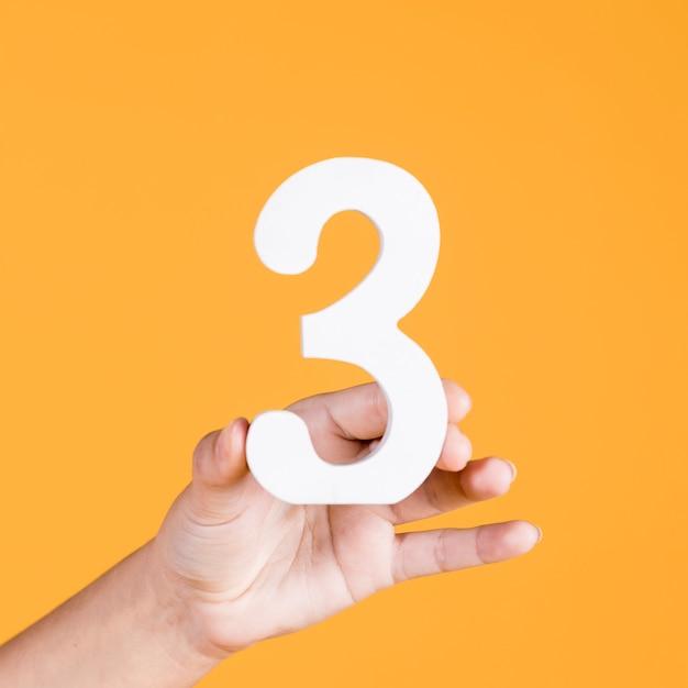 Menselijke hand die nummer 3 steunt tegen een gele achtergrond Gratis Foto