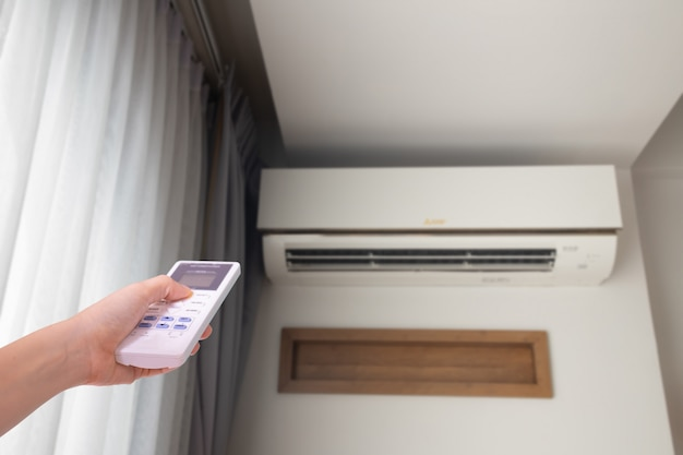 Menselijke hand dringende afstandsbedieningairconditioner in woonkamer, juiste copyspace. Premium Foto