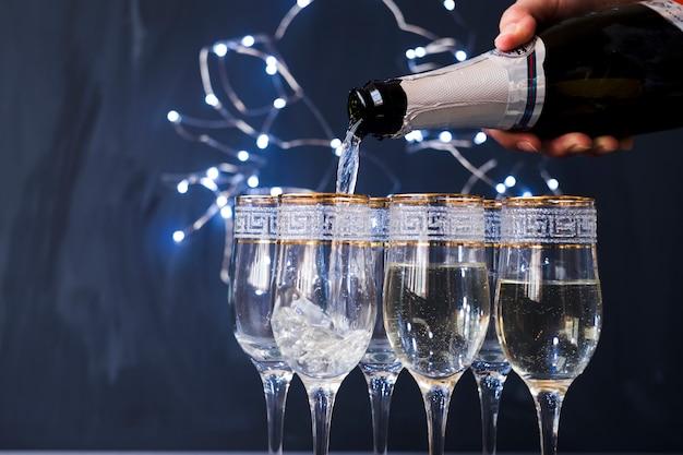Menselijke hand gieten champagne in het transparante glas op feestje Gratis Foto