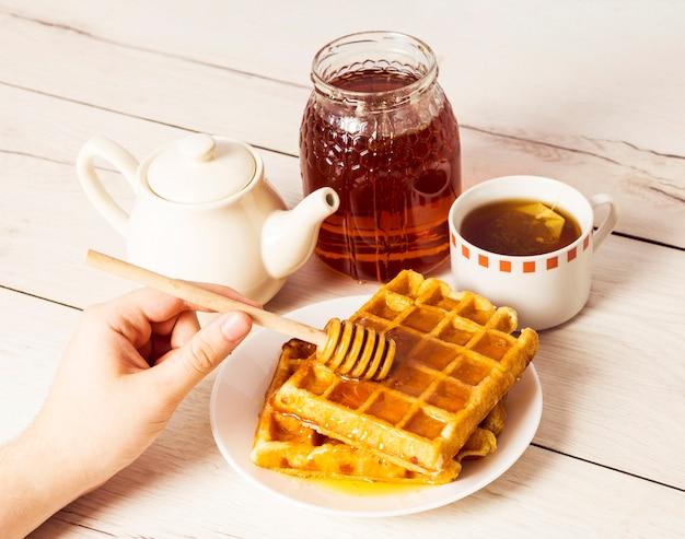 Menselijke hand gietende honing op belgische wafels die honingsdipper gebruiken Gratis Foto
