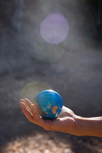 Menselijke hand met aarde planeet Gratis Foto
