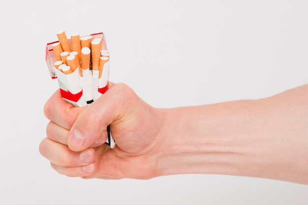 Menselijke hand met pakket van sigaretten Gratis Foto