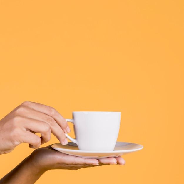 Menselijke hand met witte keramische koffiekopje en schotel Premium Foto